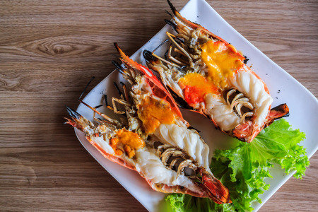 grilled large shrimp with tallow on white dish , wood background