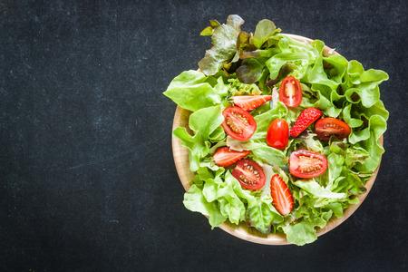 Vegetable salad in wooden bowl on blackboard Zdjęcie Seryjne