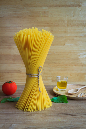 Spaghetti and tomatoes with basil and olive oil on wooden table and background