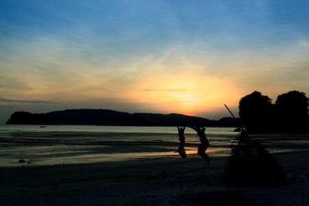 Silhouette of the loving couple, jumping on the beach at sunset