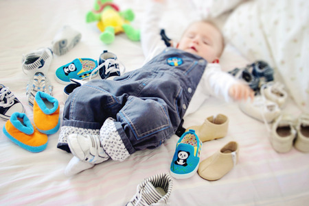 Little baby surrounded by baby shoes. Stock Photo