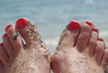 Nail polish on your toes at the beach with sand and shells on them background Sea. Concept rest.