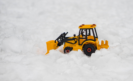 Yellow bulldozer, excavator toy snowplow placed in snow field, a concept out door childs play Reklamní fotografie