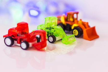 Toys red blured excavato, green loader and blured  loader, background bokeh. Concept motor skills. Stock Photo