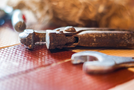 Closeup of an old, rusty plumbing wrench, blured wrench on the right. Focus on connecting screw, bokeh in the background, fiber and pliers. Stock Photo