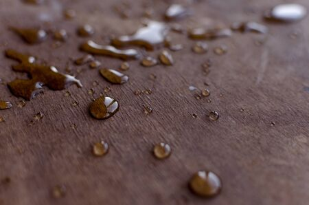 Transparent water drops are clearly visible on a mate wooden table. Reklamní fotografie