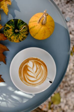 Sunny autumn day and bright cappuccino latte art , pumpkins, yellow leaves. Stock Photo
