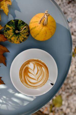 Sunny autumn day and bright cappuccino latte art , pumpkins, yellow leaves. Фото со стока