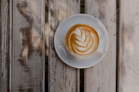 Tasty cappuccino in white cup with great latte art with place for text. Фото со стока