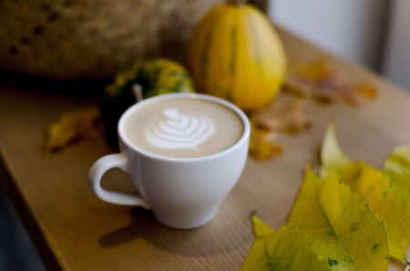 Seasonally image with soft latte art and fall decoration and pumpkin. 免版税图像