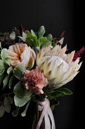 A wedding bouquet close up with white protea, carnations, peony roses, various herbs and leaves on a black background with natural light, vertically.