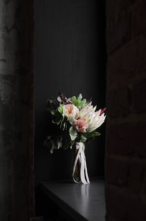 A delicate bouquet in vase with white royal protea, carnations, peony roses, various herbs and leaves on a black background with natural light, vertically.