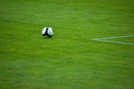 Black and white football in green grass