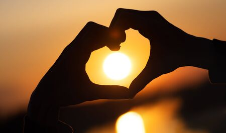 silhouette hands forming a heart shape with sunset and reflection of a solar track in the water