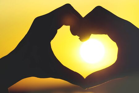 silhouette of female hands forms a heart on a sunny sunset sky and reflection in the water
