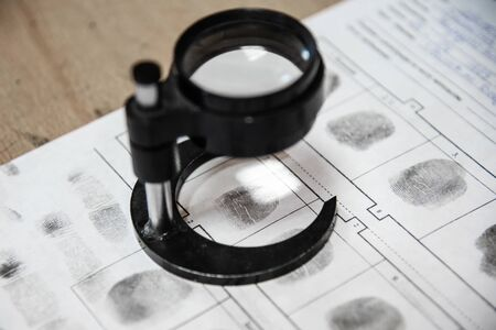 forensic scientist examines fingerprints with a magnifying glass in a laboratory. Investigation of crimes in a detective agency. database with fingerprints of criminals.