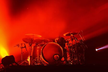 modern drum set on stage in red light at a music festival. concert poster of a popular rock band. Фото со стока