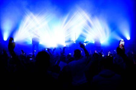 verschwommene Sicht auf die Bühne im Licht der Scheinwerfer aus der Menge bei einem Konzert. lustige Tänze auf einem Musikfestival. Plakat anzeigen Standard-Bild