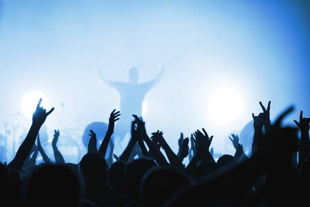 Blurred silhouettes of rock band musicians with beautiful lighting on stage and crowds at a concert. atmosphere of a music festival. light spotlights