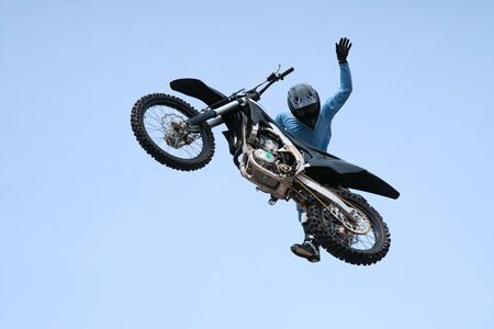 racer in a helmet on a black motorcycle is jumping against the sky. extreme motocross. stunts in the air on a motorcycle. motocross competition