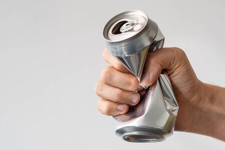 male hand squeezes an empty aluminum can for recycling. expression of anger and powerlessness. metallic packaging for drinks Stockfoto