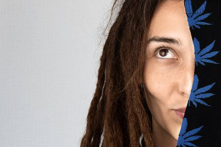 funny girl with dreadlocks holds a hemp print sock on her face. stereotypes about people with dreadlocks. public opinion. show off shopping. hemp