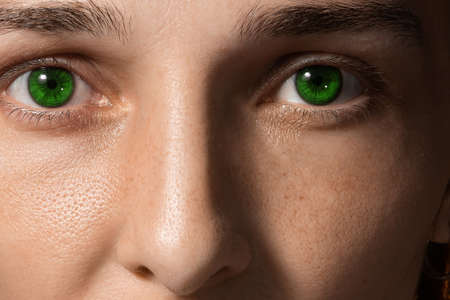 close-up face of a girl with green lenses and freckles. Girl without makeup. clean fresh skin