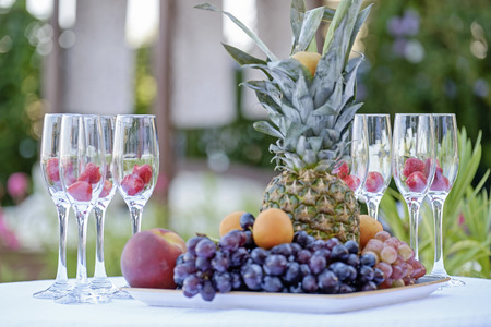 Exotic fruits and champagne glasses with berries on the table 2 Stock Photo