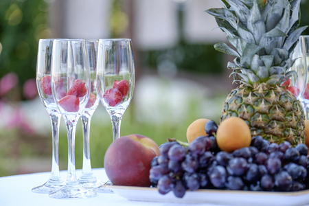 Exotic fruits and champagne glasses with berries on the table 1 Stock Photo