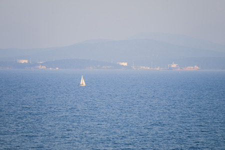 Small white yacht in black sea panorama