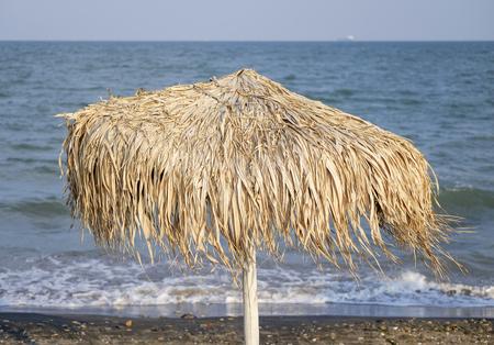 Straw umbrella on sandy beach