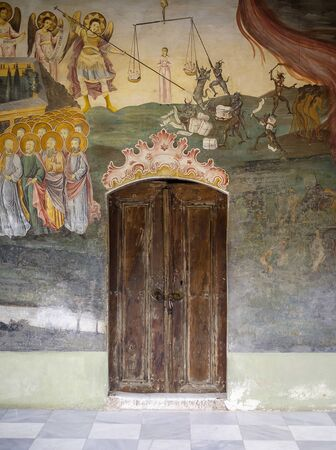 Door to the old monastery surrounded by old fresco 写真素材 - 128890559