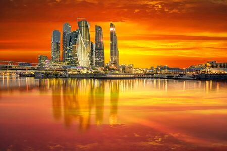 Moscow City in the colorful orange rays of the sunset. View from the river 스톡 콘텐츠