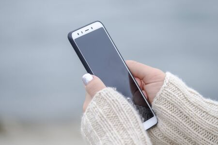 Woman holding a white smartphone close up 1