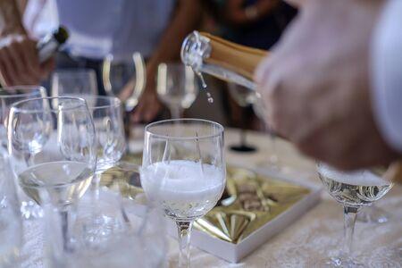 Mann gießt Champagner in Gläser auf Tisch 3