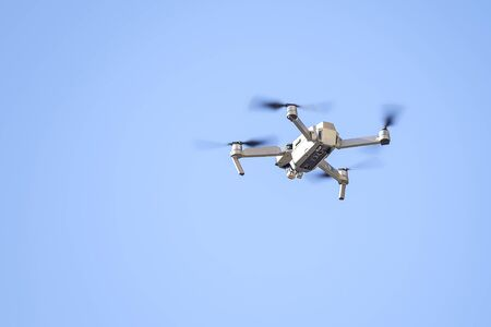 Drone flies in the blue sky close up 1
