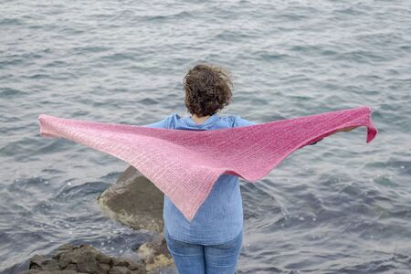 A woman in a knitted scarf stands on sea coast 4