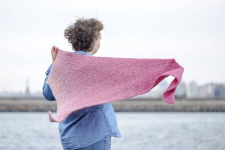 A woman in a knitted scarf stands on sea coast 3
