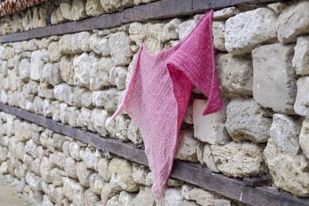 A handmade knitted magenta scarf on an old stone wall 2