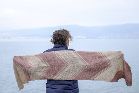 A woman in a knitted scarf stands on sea coast 1