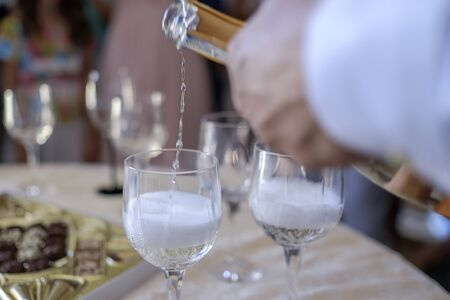 Man pours champagne into glasses on table 2