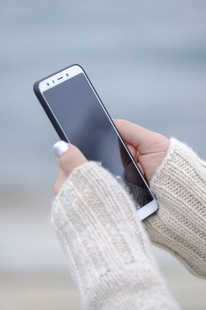 Woman holding a white smartphone close up 3
