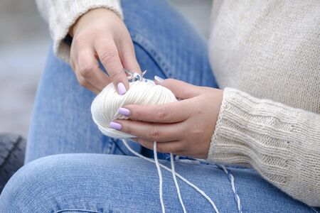 A woman and a white yarn. Woman knits on the coast 1 Stock fotó