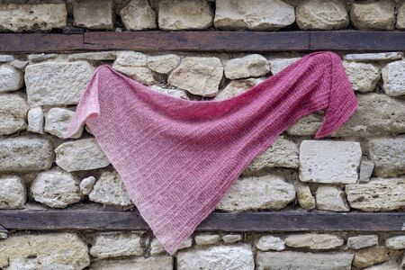 A handmade knitted magenta scarf on an old stone wall 1