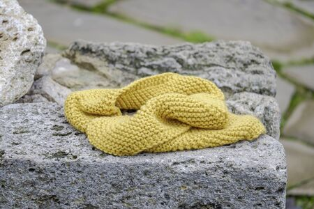 Knitted yellow scarf on a stone wall closeup 3