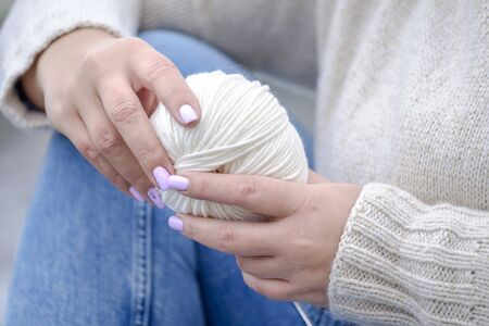 A woman and a white yarn. Woman knits on the coast 5