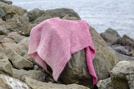 Knitted magenta scarf on a stone on the beach 1