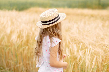 girl in a wheat field. girl in a hat. child in the village.