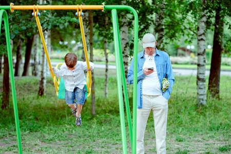 dad in the playground. Dad looks at the phone. The boy is riding on a swing.