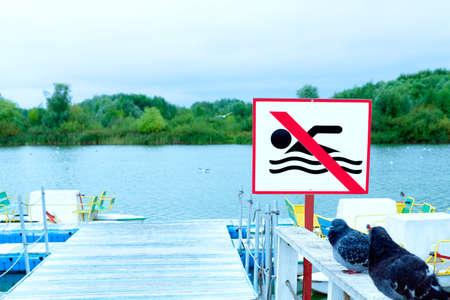 no swimming sign on the beach. lake embankment
